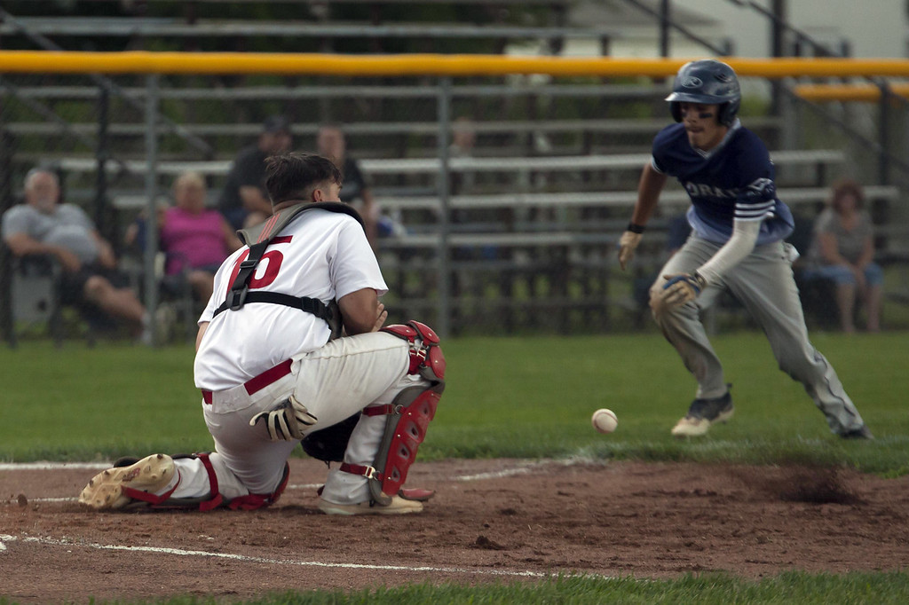 . Jen Forbus - The Morning Journal  Lorain\'s Yandel Ramirez races the throw to Elyria catcher Max Petyon at home plate to score the Titan\'s lone run of the game.