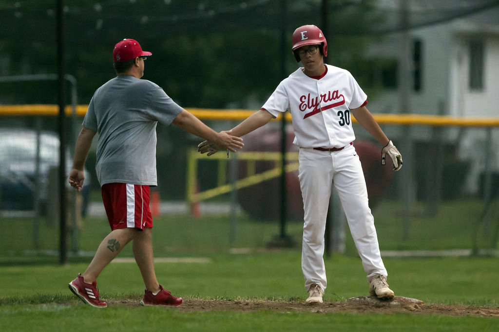 . Jen Forbus - The Morning Journal Elyria\'s Gage Barbee gets a congratulatory hand slap from Coach Piazza at third base.