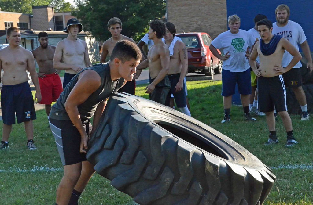 . Paul DiCicco - The News-Herald Freshman Mike Moon lifts the truck tire during the truck-tire-relay at Devil Dog Soldier workouts on July 27.