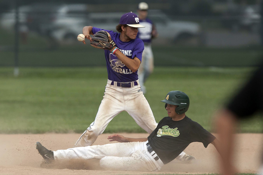 . Jen Forbus - The Morning Journal  Keystone short stop Cameron Emerick takes aim to throw the ball to first as Amherst\'s Jason Monos slides into second.