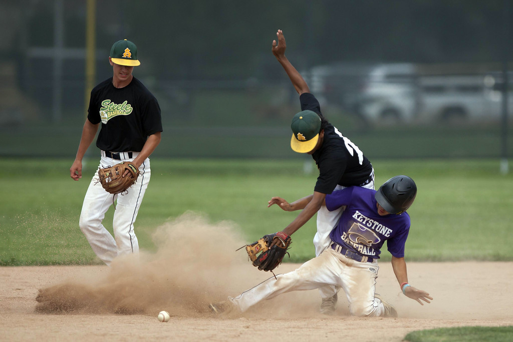 . Jen Forbus - The Morning Journal Amherst short stop Josh Qualls falls over Keystone baserunner Cameron Emerick trying to maintain control of the baseball.