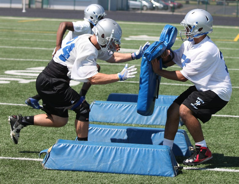 Randy Meyers - The Morning Journal<br> Midview running backs take part in blocking drills during the first full football practice of the season on July 31.
