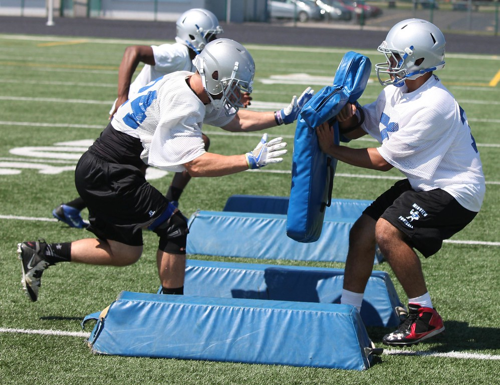 . Randy Meyers - The Morning Journal<br> Midview running backs take part in blocking drills during the first full football practice of the season on July 31.