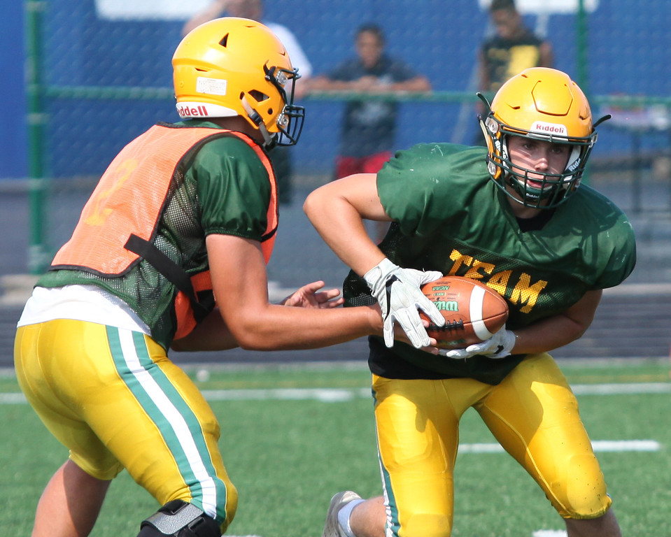 . Randy Meyers - The Morning Journal<br> Amherst quarterback Matt Fairchild hands off to Jonathan West during a scrimmage against Lorain on Aug. 11.