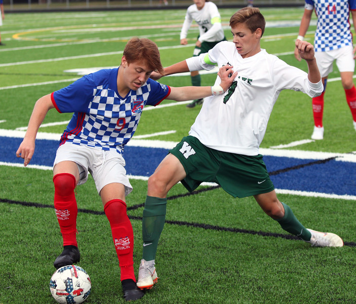 Randy Meyers - The Morning Journal<br> Westlake's Ben Carson attempts to kick the ball away from Bay's Matt DeCapua at the sideline during the first half on Aug. 17.