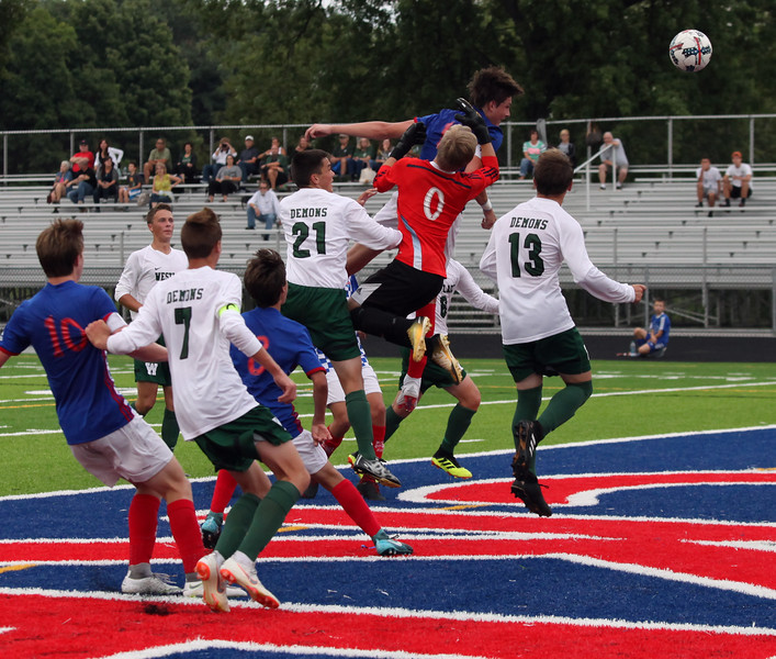 Randy Meyers - The Morning Journal<br> Bay's Cade Gergye (center) heads a corner kick for a goal against Westlake during the first half on Aug. 17.