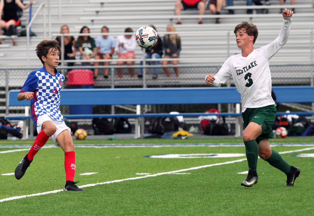. Randy Meyers - The Morning Journal<br> Bay\'s Danny Kruzer and Westlake\'s Vincent Napoli converge on a high bounce near midfield during the first half on Aug. 17.