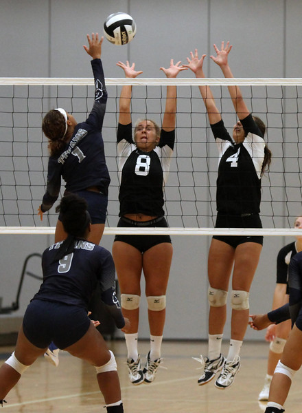 Randy Meyers - The Morning Journal<br /> Lorain's Julissa Williams spikes  over Columbia's Ashley Krupinski (left) and Amelia Hritz during the second  set on Saturday