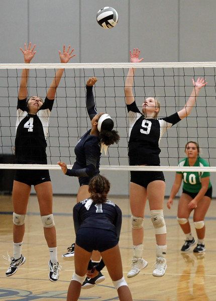 Randy Meyers - The Morning Journal<br /> Lorain's Sydney Patterson taps the  ball over Amelia Hritz (left) and Morgan Davis of Columbia on Saturday