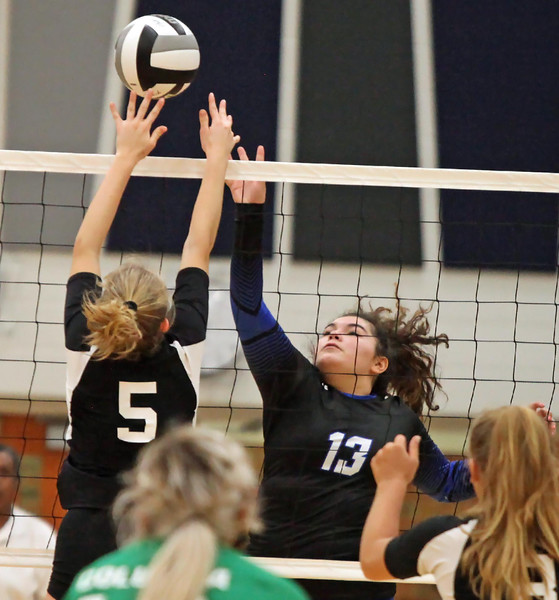 Randy Meyers - The Morning Journal<br /> Midview's Mackenzie Cline spikes  the ball over Laci Riley of Columbia during the first set on Saturday.