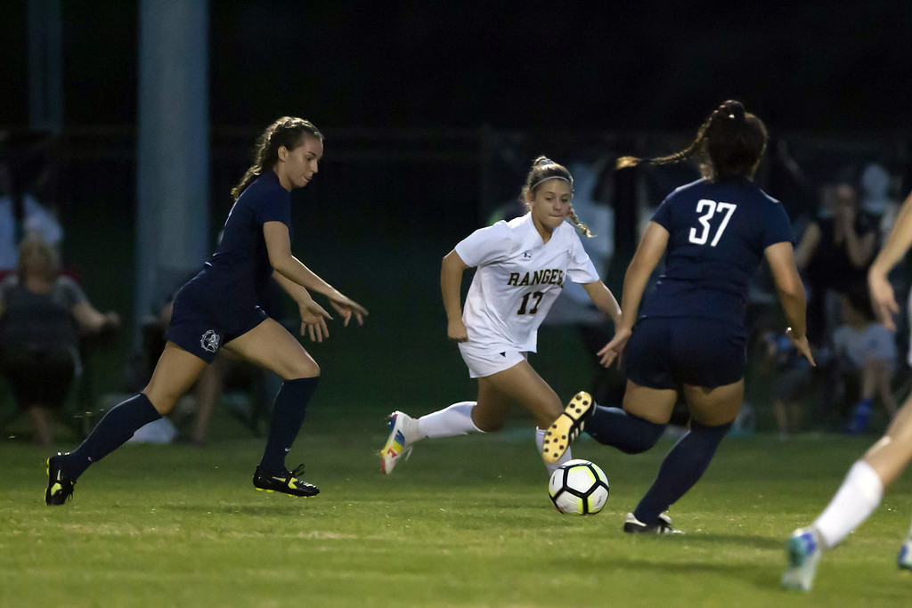 . Jen Forbus - The News-Herald As Olmsted Falls\' Mia Colozza dribbles downfield, North Ridgeville\'s Abby Bernhardt closes in to try and steal the ball.