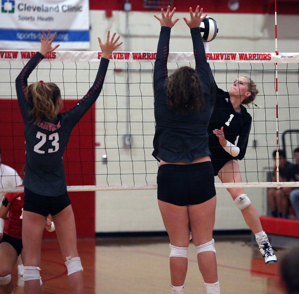 Randy Meyers - The Morning Journal<br> Sydney LaPointe of Lutheran West spikes the ball at Fairview's Maeve Mesaros (right) and Jade Peace during the second set on Sept. 6.