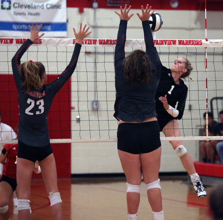 . Randy Meyers - The Morning Journal<br> Sydney LaPointe of Lutheran West spikes the ball at Fairview\'s Maeve Mesaros (right) and Jade Peace during the second set on Sept. 6.