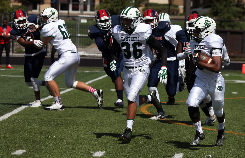. Randy Meyers - The Morning Journal<br> Elyria Catholic running back Jonah Baker runs left and picks up blockers against CCC on Saturday afternoon.