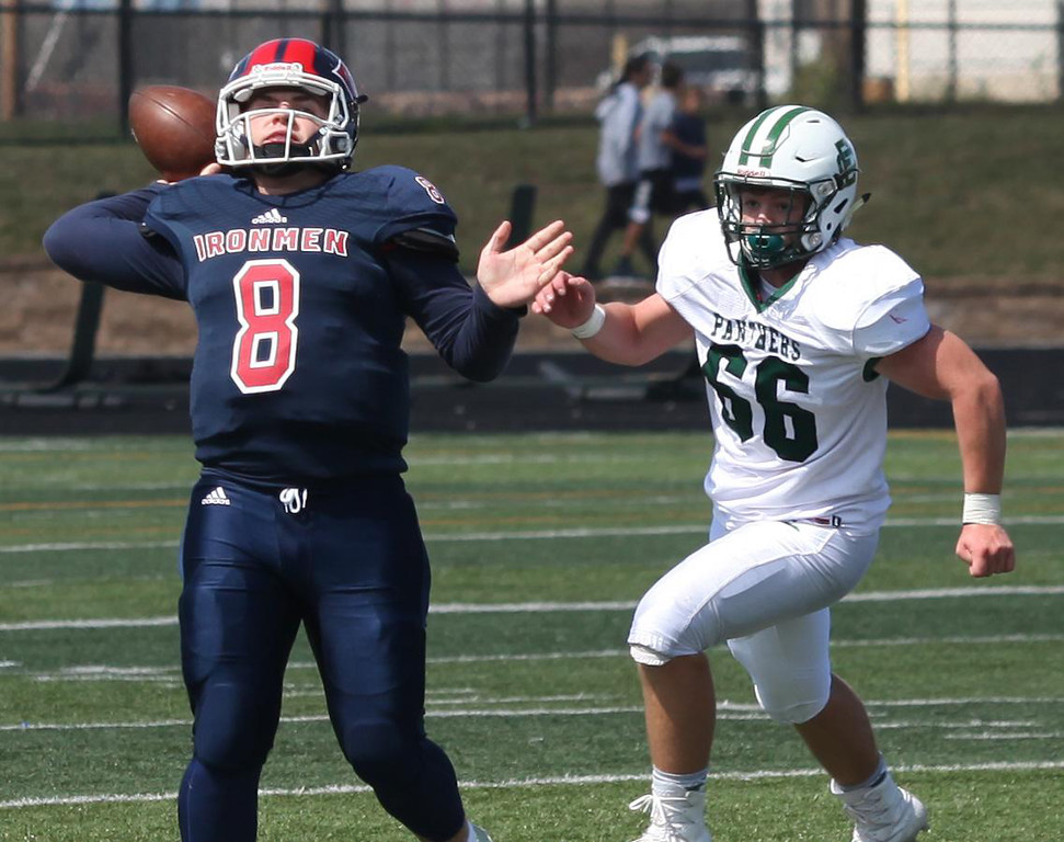 . Randy Meyers - The Morning Journal<br> CCC quarterback J.C. Dunn throws a deep ball despite the pass rush from Nick Pagenstecher of Elyria  Catholic on Saturday.