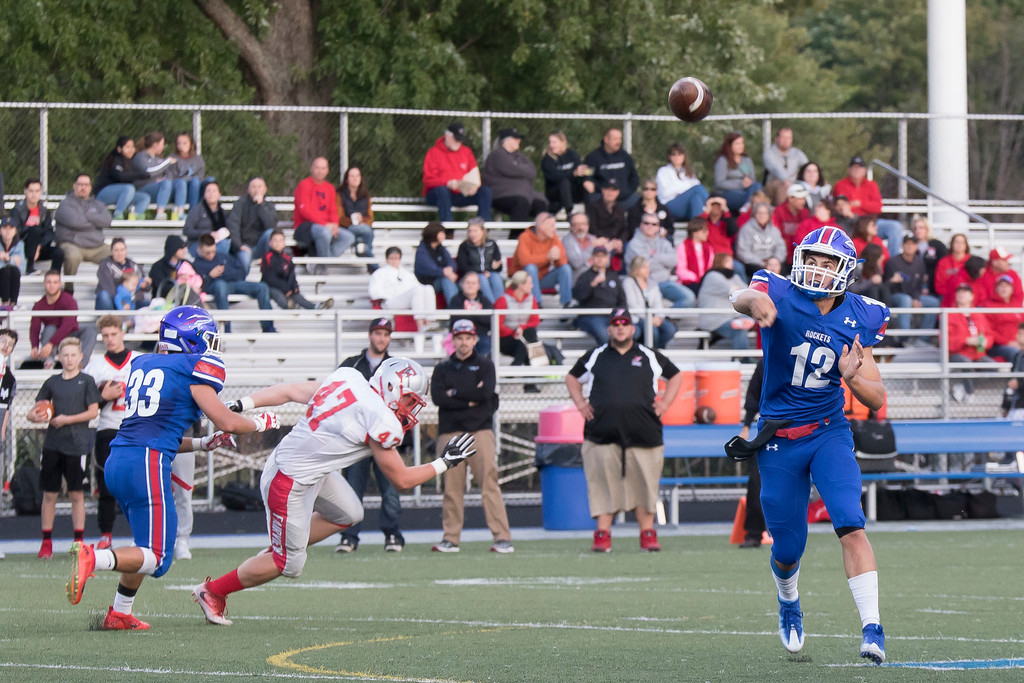 . Jen Forbus - The Morning Journal<br> Bay quarterback Connor Shell throws for an incomplete pass as Fairview\'s Colin Hayes tries to make his way past Mark Olsen on Sept. 8.