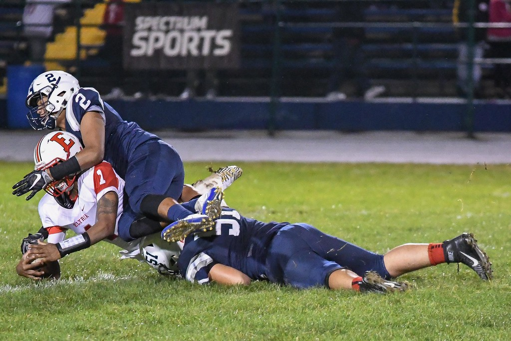 . Eric Bonzar�The Morning Journal<br> Elyria tailback Dontae Beckett (1) is brought down by Lorain\'s Davion Dower (2) and Kelvin Torres (51),  Sept. 7, 2017.