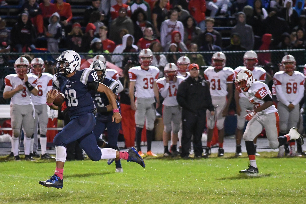 . Eric Bonzar�The Morning Journal<br> Lorain Titans running back Mikey Harrell (18) rushes in to the end zone, uncontested,  Sept. 7, 2017.