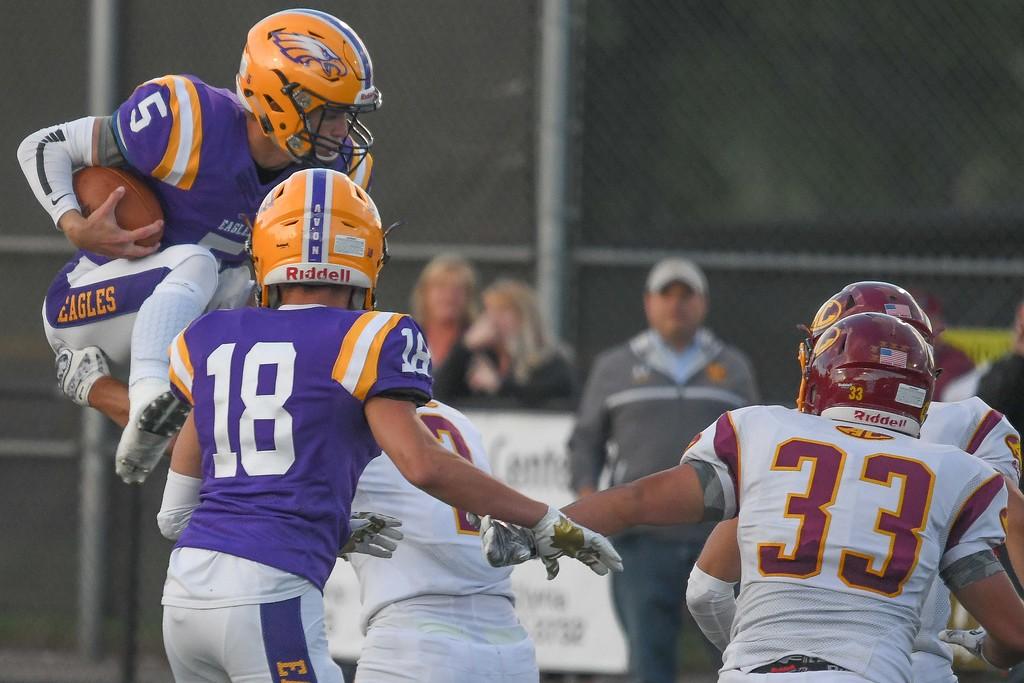 . Eric Bonzar�The Morning Journal<br> Avon quarterback Ryan Maloy (5) tries to hurdle the Avon Lake defense, on a keeper, Sept. 8, 2017.