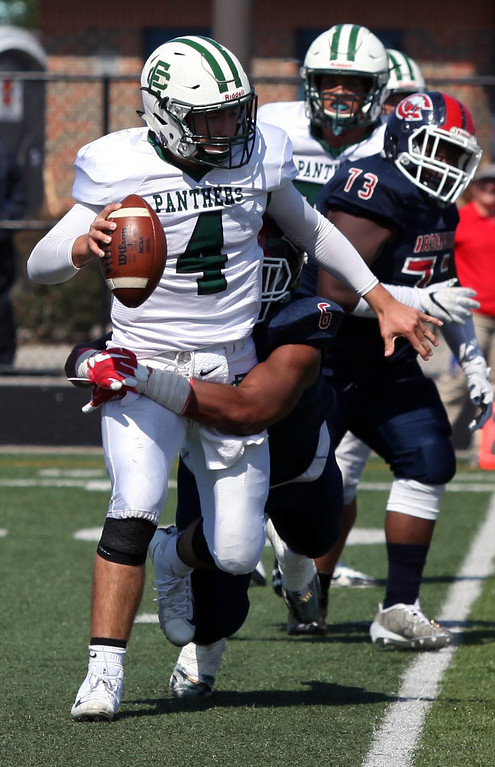 . Randy Meyers - The Morning Journal<br> Elyria Catholic quarterback Cameron Engrish is sacked by Anthony Billups of Cleveland Central Catholic during the third quarter on Saturday.