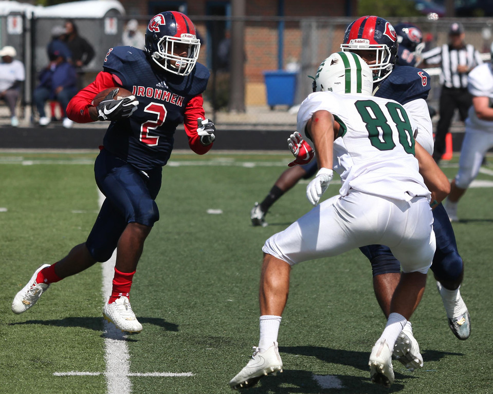 . Randy Meyers - The Morning Journal<br> Marvin Minger of Cleveland Central Catholic picks up a block against the Elyria Catholic defense and runs for a gain on Saturday.