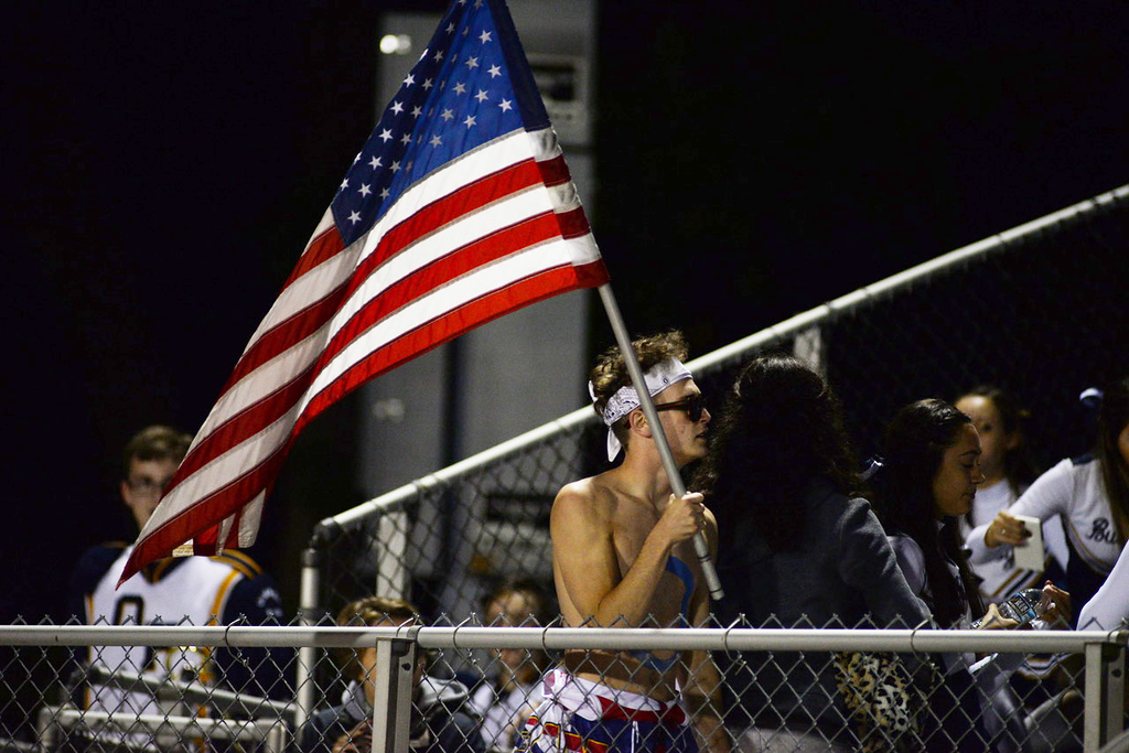 . Aimee Bielozer - The Morning Journal<br> An Olmsted Falls fan carries an American flag into the student section on Sept. 8.