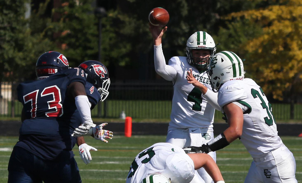 . Randy Meyers - The Morning Journal<br> Elyria Catholic quarterback Cameron  Engrish throws a short pass to running back Leighton Bajoff amid the pass rush by CCC during the third quarter on Saturday.
