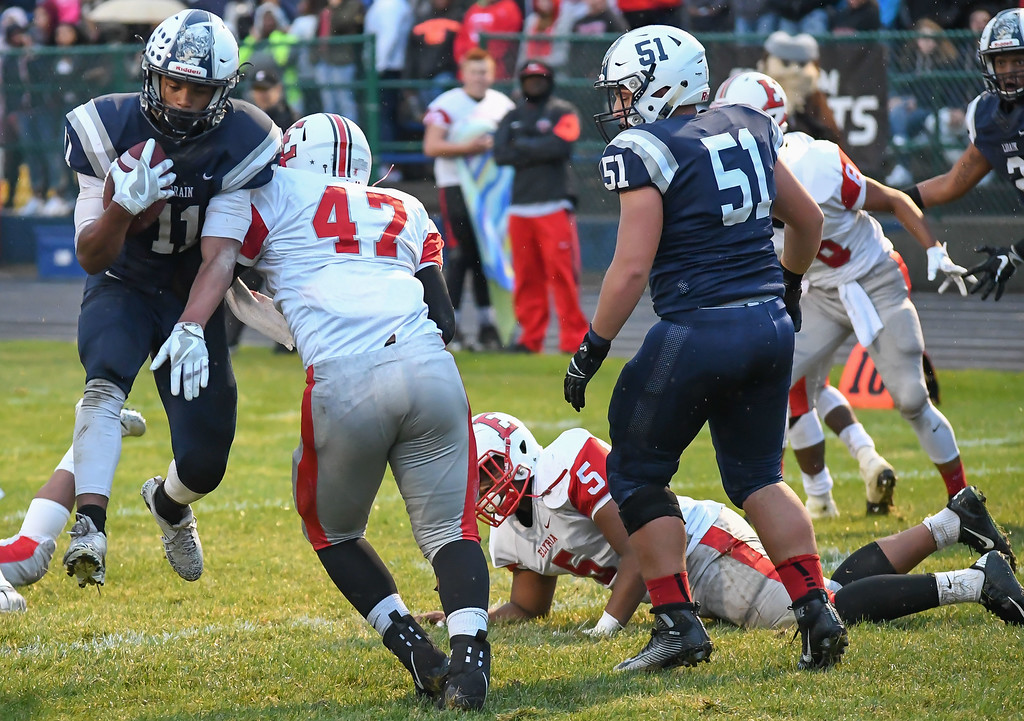 . Eric Bonzar�The Morning Journal<br> Lorain running back Daylin Dower (11) leaps past Elyria linebacker Lewis Aguilar (47), on his way to the end zone, Sept. 7, 2017.