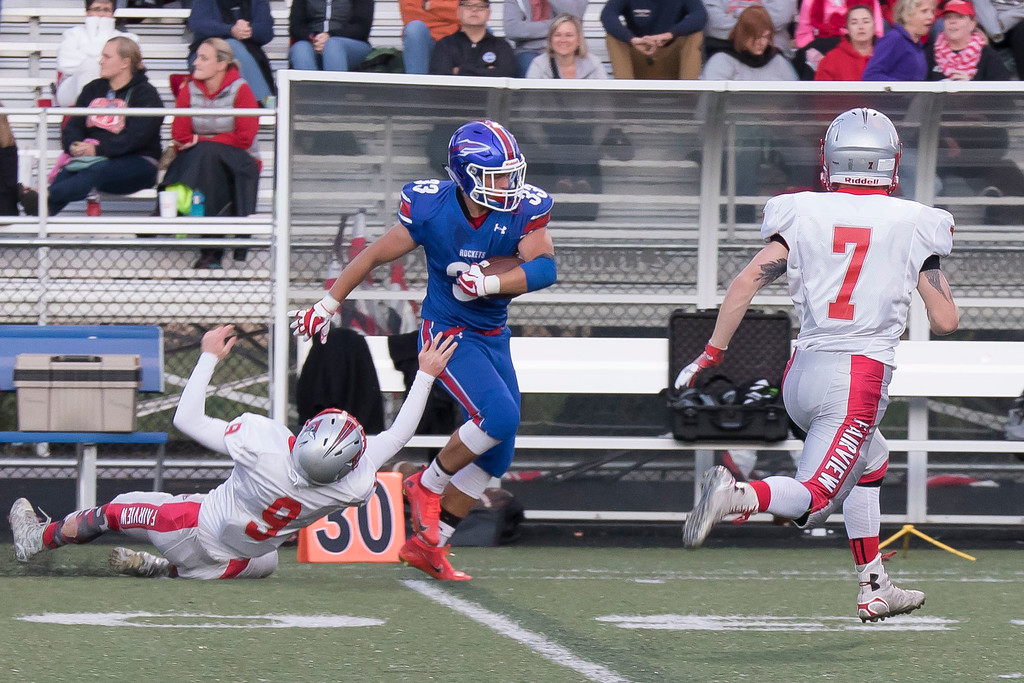 . Jen Forbus - The Morning Journal<br> Bay\'s Mark Olson breaks a tackle as Fairview\'s Quintin Pachuta (7) closes in on Sept. 8.