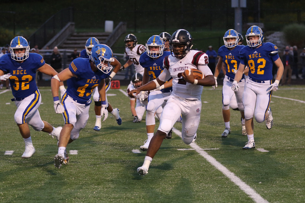 . David Turben - The News-Herald University quarterback Jayden Cunningham runs the ball but is swarmed by the NDCL defense.