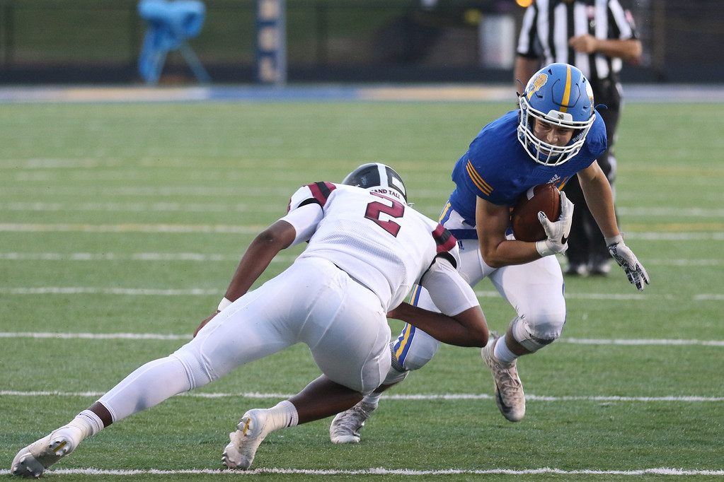 . David Turben - The News-Herald NDCL defeated University 38-7 on Sept. 8. NDCL running back Kyle Medves (21) is tackled by University\'s Jayden Cunningham.