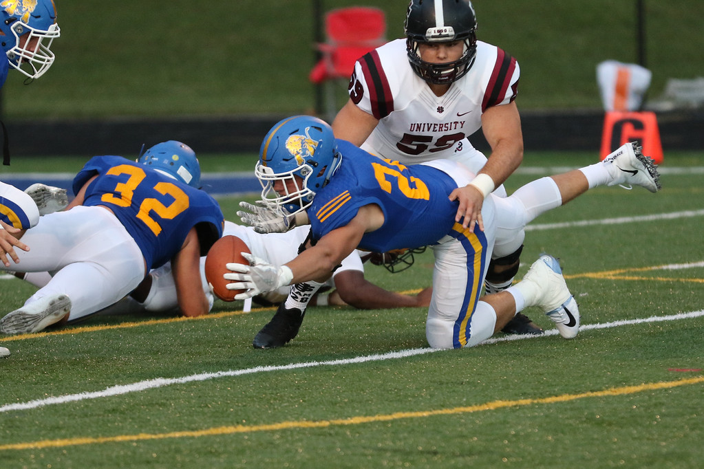 . David Turben - The News-Herald NDCL\'s Zach Urda (24) recovers a University fumble inside the 10 yard line.