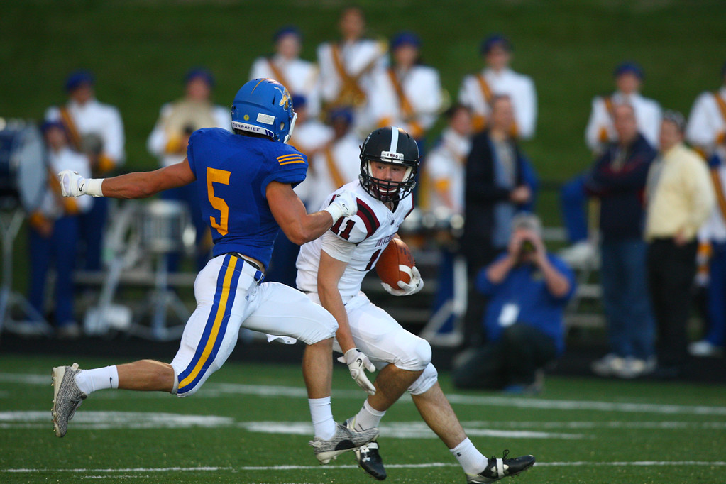 . David Turben - The News-Herald University wide receiver Jake Kapp (11) tries to avoid NDCL\'s Josh Peroni (5).