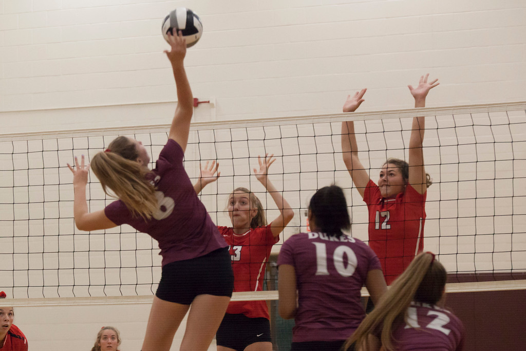 . Jen Forbus - The Morning Journal<br> Wellington\'s Alexis Lehmkuhl hits the ball over the net as Fairview\'s Abby Kuyper and Jade Peace leap to block on Sept. 8.