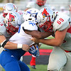 David Turben - The News-Herald<br /> Mentor Defensive Lineman Kyle Ulshafer (69) and James Pedley (44) tackle a St Xavier running back for a loss.