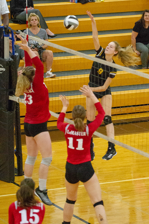 . Barry Booher - The News-Herald Riverside\'s Olivia Bell spikes on Chardon\'s (23) Audrey Kostelac and (11) Isabelle LeMaster.