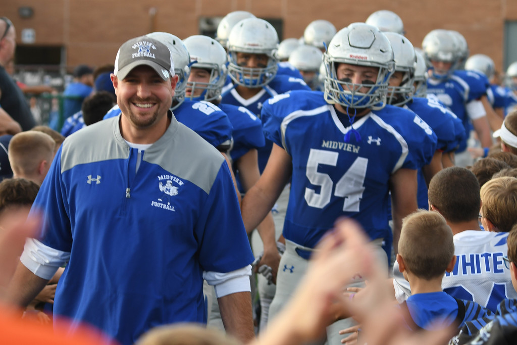 . Eric Bonzar�The Morning Journal<br> Head Coach DJ Shaw and the Midview Middies make their way through a sea of fans before kicking off against the Amherst Comets, Sept. 15, 2017.