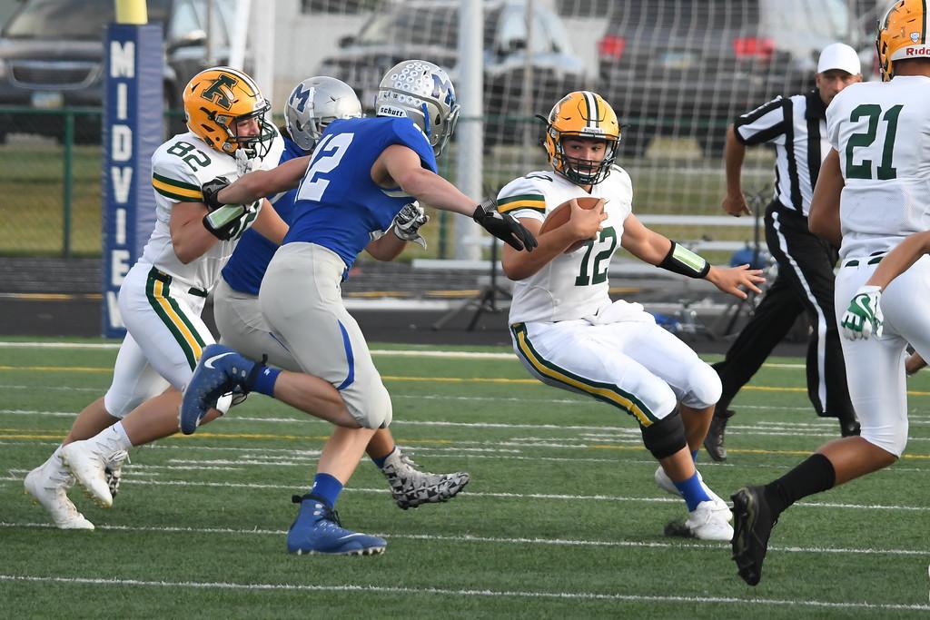. Eric Bonzar�The Morning Journal<br> Amherst quarterback Matt Fairchild (12) cuts for a hole in the Midview defense, Sept. 15, 2017.