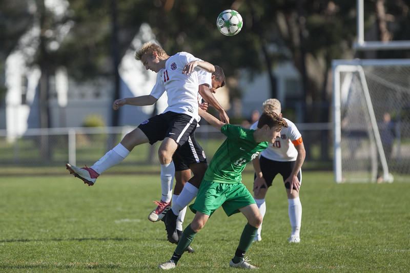 Jen Forbus - The Morning Journal<br /> Elyria's Joshua Rader (11) and Malik Holt vie with Elyria Catholic's Jake Records in a leap for a header.