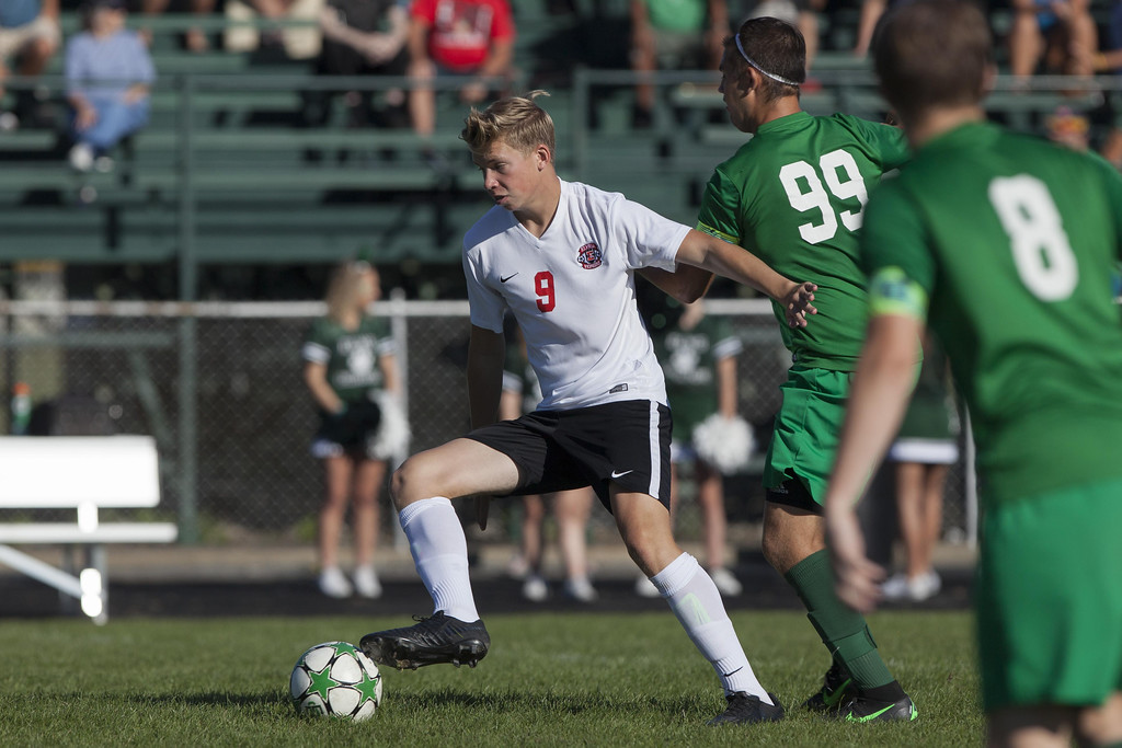 . Jen Forbus - The Morning Journal  Allen Prechtel of Elyria employs smart footwork to keep possession of the ball as EC\'s Asa Kempton tries to take it away.