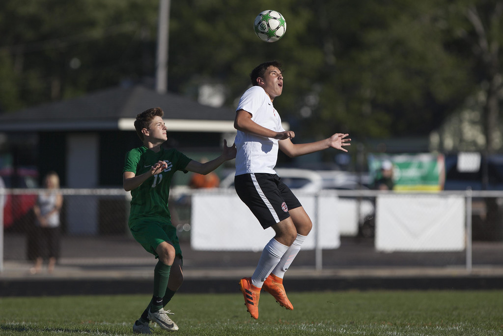 . Jen Forbus - The Morning Journal Elyria\'s Colton Hyde gets his head on the ball as Elyria Catholic\'s Jake Records looks on.