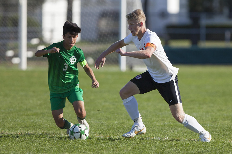 Jen Forbus - The Morning Journal<br /> EC's Andrew Muzilla tries to keep possession of the ball as Elyria's Jack Bailey closes in on him.