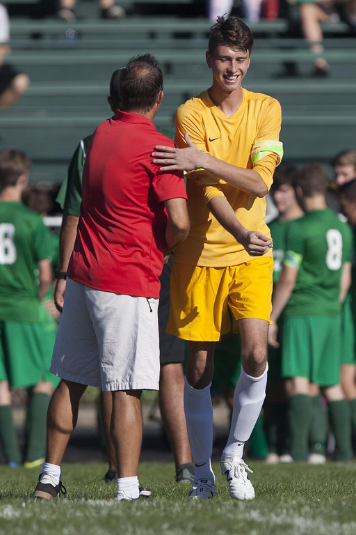 . Jen Forbus - The Morning Journal Elyria High School coach Brett Heighberger wishes Elyria Catholic goalkeeper, Bryce Hileman, good luck before the start of the game September 15.
