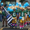 Randy Meyers - The Morning Journal<br /> The Amherst football team pauses during a moment of silence  in rememberance of fallen State Trooper Kenneth Velez. Trooper Valez's son, Christian, holds the flag.