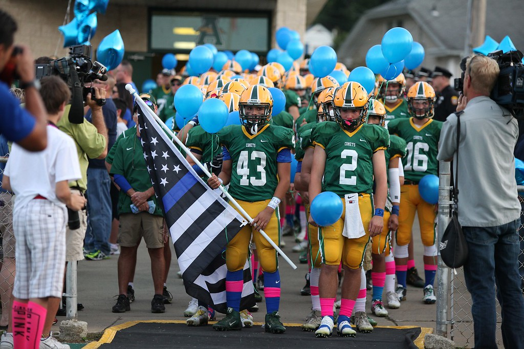 . Randy Meyers - The Morning Journal The Amherst football team pauses during a moment of silence  in rememberance of fallen State Trooper Kenneth Velez. Trooper Valez\'s son, Christian, holds the flag.