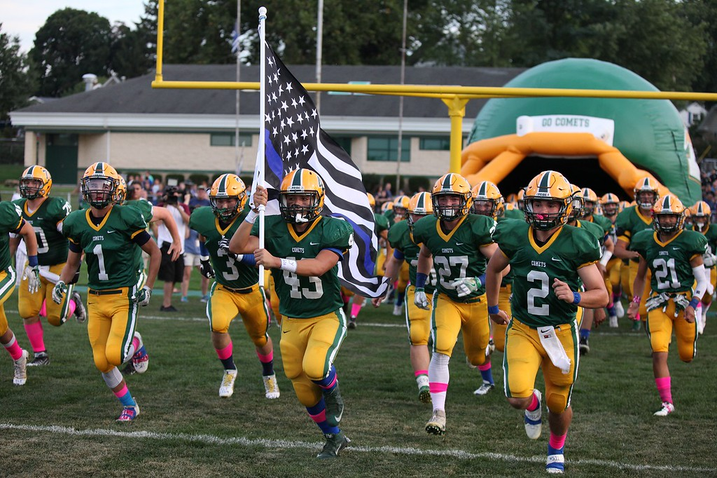 . Randy Meyers - The Morning Journal Christian Velez leads the Amherst Comets onto the field and holds the Fallen Officers Memorial Flag in honor of his father, Trooper Kenny Valez, on Sept. 16. Tooper Valez was killed in the line of duty on Sept. 15.