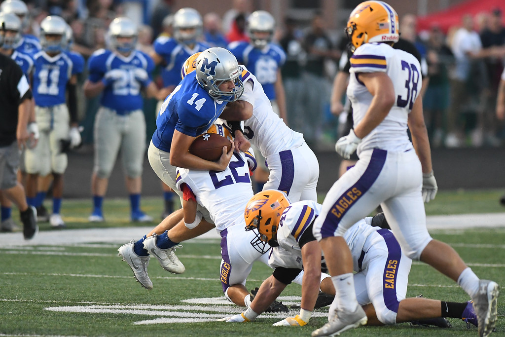 . Eric Bonzar�The Morning Journal Midview quarterback Dustin Crum (14) is lifted off his feet by the Avon Eagles defense, Sept. 16, 2016.