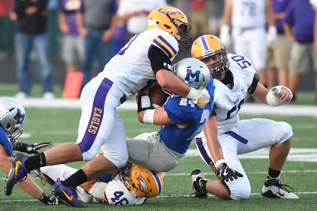 . Eric Bonzar�The Morning Journal Midview\'s Alec Forrer (24) is wrapped up by Avon defender Will Kocar (46), Sept. 16, 2016.