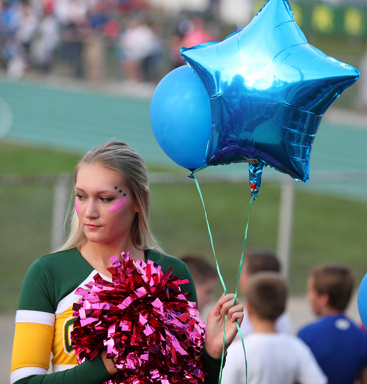. Randy Meyers - The Morning Journal Amherst cheerleader Maycee Frederick pauses just before the national anthem on Friday night.