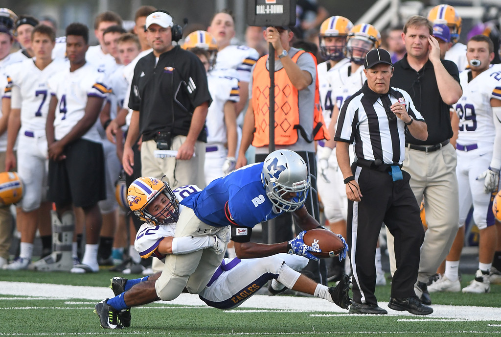 . Eric Bonzar�The Morning Journal Midview\'s Keith Johnson (2) fights for extra yards as he\'s wrapped up by Avon\'s Cole Lindsay (22), Sept. 16, 2016.